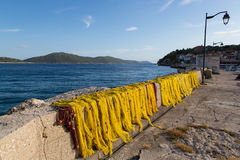Yellow fishnet drying in the sunlight in harbour royalty free stock photos