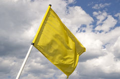 Yellow flag. Yellow flag on a background of the dark blue sky with clouds Royalty Free Stock Images