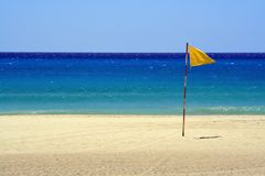 Yellow flag at beach Stock Images