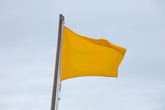 Yellow flag on the beach Stock Image