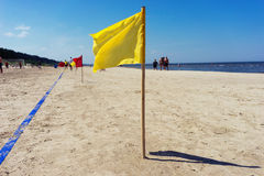 Yellow flag and the blue line in the sand beach Stock Images
