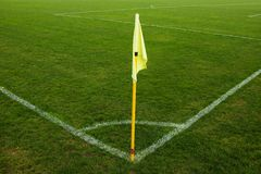 Yellow flag in corner of natural football playground, lazy wind blowing Royalty Free Stock Image