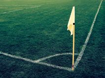 Yellow flag in corner of natural football playground, lazy wind blowing Stock Photo