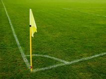 Yellow flag in corner of natural football playground, lazy wind blowing Royalty Free Stock Images