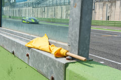 Yellow flag danger signal for racing motor sport. Yellow flag danger signal for motor sport with racing car blurred in background on track royalty free stock images