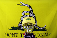 Yellow Flag. Glass head wearing don't tread on me baseball hat with confederate flag scarf with yellow Gadsden flag background Stock Photo