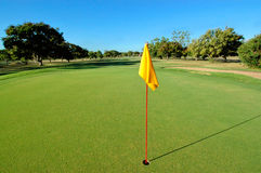 Yellow flag on golf green. On a warm summers day without a cloud in the sky all that could be seen on this hole was bright green grass freshly mowed,trees and a Royalty Free Stock Photos