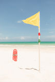 Yellow flag and red plactic lifeguard tube Stock Images
