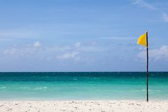 Yellow flag stands on the beach. Stock Photography