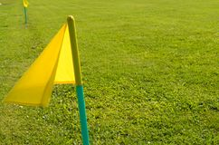 Yellow flags on the green grass of a football playing field. Stock Images