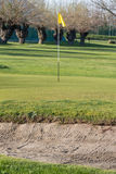 Yellow flagstick in golf course in sunny day Stock Photo