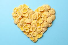 Yellow flakes in the shape of a heart on a blue background. I like breakfast cereal. Yellow flakes in the shape of a heart on a blue background. I like royalty free stock photography