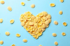 Yellow flakes in the shape of a heart on a blue background. I like breakfast cereal. Yellow flakes in the shape of a heart on a blue background. I like stock photos