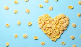 Yellow flakes in the shape of a heart on a blue background. I like breakfast cereal. Yellow flakes in the shape of a heart on a blue background. I like royalty free stock images