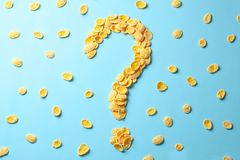 Yellow flakes in the shape of a question mark on a blue background. How to choose cereal for breakfast or what make cereal. Yellow flakes in the shape of a royalty free stock photos