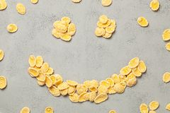 Yellow flakes in the shape of smiling face on blue background. I like breakfast cereal. Yellow flakes in the shape of smiling face on blue background. I like royalty free stock photos