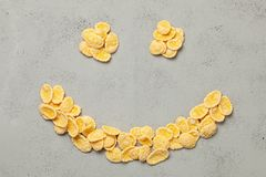 Yellow flakes in the shape of smiling face on blue background. I like breakfast cereal. Yellow flakes in the shape of smiling face on blue background. I like stock photo