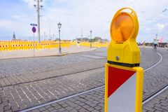 Yellow flashing light standing at road construction site. Road works concept. Royalty Free Stock Photo