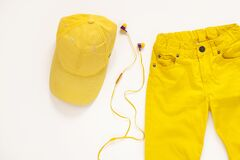 Yellow flatlay jeans, baseball cap and headphones on white background copy space,top view.Spring summer fashion clothing