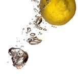 Yellow flight. Lemon in the flight surrounded and followed by water bubbles; isolated on white background; copy space provided Stock Image