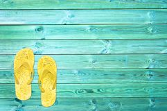 Yellow flip flops on blue planks, summer concept background. With copy space stock images