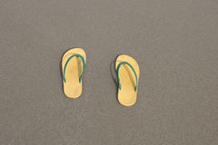 Yellow flip-flops footware pair on the beach sand Royalty Free Stock Photos