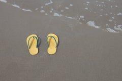 Yellow flip-flops footware pair on the beach sand Stock Photo