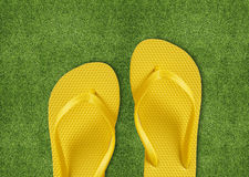 Yellow Flip Flops on green grass Stock Photography