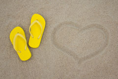 Yellow flip flops and heart on sandy beach Royalty Free Stock Photo