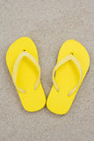 Yellow flip flops on the sand of a tropical beach Stock Image