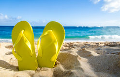 Yellow flip flops on the sandy beach Stock Image
