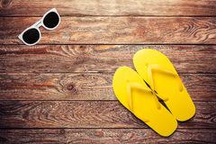 Yellow flip flops and sunglasses. On a wooden background stock photos