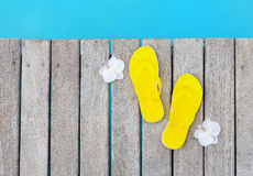 Yellow flip flops by the swimming pool Royalty Free Stock Image