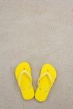 Yellow flip flops on the white beach sand Stock Image