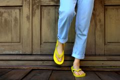 Yellow Flip Flops. Woman Legs and Feet Wearing Yellow Sandals Standing on Wooden Floor and wooden Wall Stock Photos