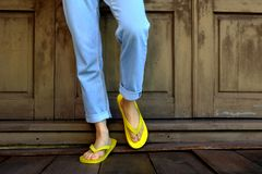 Yellow Flip Flops. Woman Legs and Feet Wearing Yellow Sandals Standing on Wooden Floor and wooden Wall Royalty Free Stock Photo