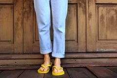 Yellow Flip Flops. Woman Legs and Feet Wearing Yellow Sandals Standing on Wooden Floor and wooden Wall Stock Images