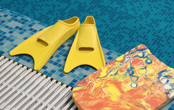 Yellow flippers with board. Yellow flippers and swimming board on the coast of swimming pool Stock Photos