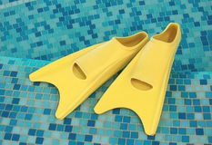 Yellow flippers on the coast. Of swimming pool Royalty Free Stock Photos