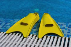 Yellow flippers on coast of sw. Imming pool Stock Photo