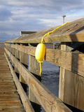 Yellow Float. A little yellow float on a little yellow rope, hanging over the wooden railing of a fishing pier. Taken on the waterfront in Tacoma, Washington Stock Photo