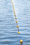 Yellow float floats on a rope floating in the sea.  stock image