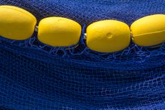 Yellow floats in a row over a deep blue fishing nets stock photography
