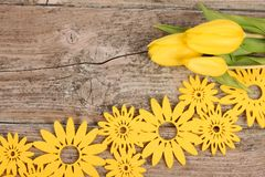 Yellow floral decoration on wooden background. With tulips royalty free stock photos