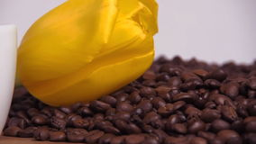 Yellow flower on coffee beans. Yellow tulip on coffee beans. stock video footage