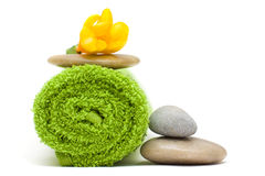 Yellow flower, green towel and river stones Royalty Free Stock Photography