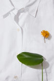 Yellow flower in a pocket. White cotton shirt with a yellow flower in a breast pocket, the minimalistic concept of spring Royalty Free Stock Photos