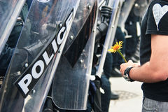 Yellow Flower and Police G8/G20 Protest. The yellow follow is holding for peace and human rights.  The police is blocking the protestor from enter the security Royalty Free Stock Images