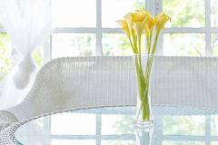 Yellow flower in vase on table and window sill background. Vintage style decorate