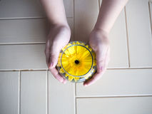 Yellow flower in water glasses with hand holding. On wood table Royalty Free Stock Photos